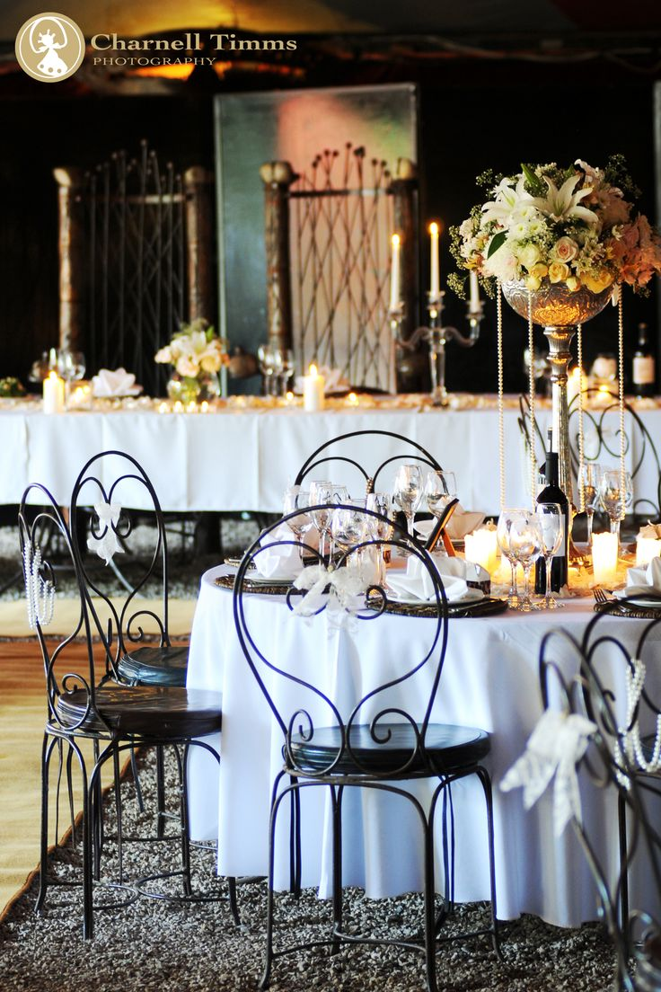 Wedding flowers around wrought-iron table settings. Charnell Timms Photography
