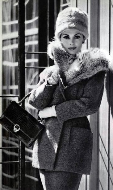 A model wearing a tweed suit by Carven, with a handbag and gloves by Hermès (Paris 1959).