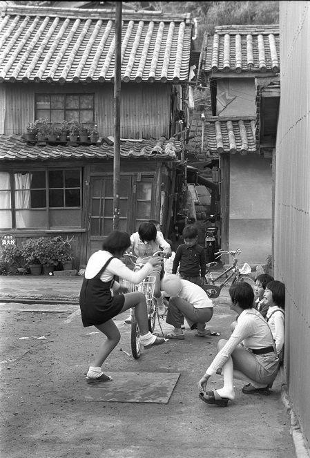 昭和の古い町並み写真展その48「子供の遊ぶ風景3」岡山県倉敷市下津井本瓦葺きの民家の空き地で遊ぶ子供を撮影昔は公園や運動場の整備もなく少しの空きスペースが子供の遊び場であった。少ないスペースでどんな遊びをするかも子供の知恵の出しどころでもあった。現在は子供の写真撮るにも親が付いていて肖像権があり安易に子供の写真が撮れなくなった。特に女の子は撮るのが難しい。自然体の子供を撮るのが難しい、祭りや行事の子供を可愛く撮った写真ばかりになっている。写真家の田沼武能氏のように昔から子供の写真ばかり撮ってきた人もいる。時代の流れとともに一貫したテーマで撮り続けた人の写真は説得力があり記録としても優れている。我々も建物だけを長年撮り続けるとか。鉄道ばかり撮り続ける事は出来たはずだがこの歳になるで気付かなかった。しかし、世の中に...記昭和の古い町並み写真展その48「子供の遊ぶ風景3」岡山県倉敷市下津井