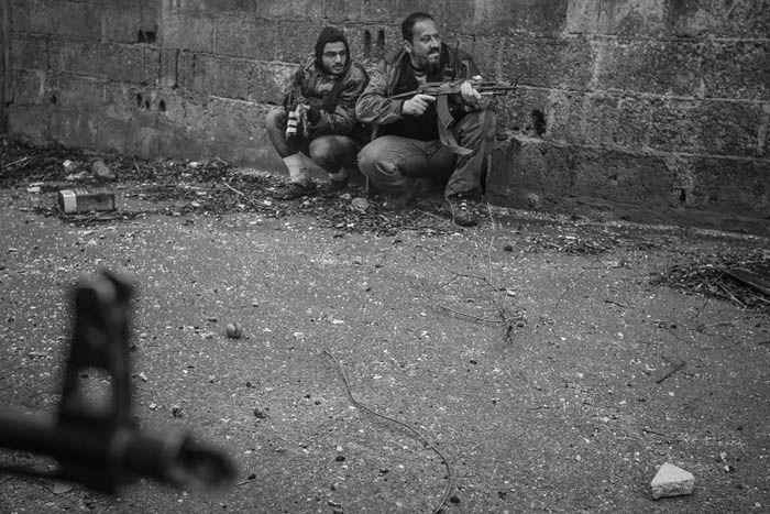 Ribelli siriani prendono posizione mentre preparano un attacco ad un checkpoint dell'esercito siriano nel quartiere di Ain Tarma, a Damasco. Gli uomini saranno presto colpiti dal fuoco di un cecchino.