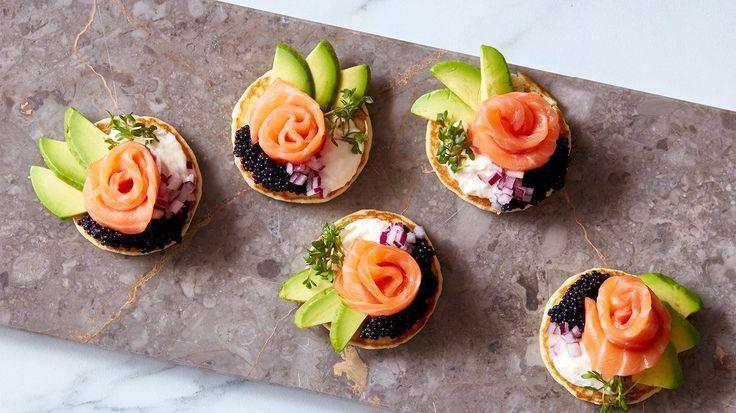 Imponér dine gæster med disse nemme og dekorative blinis med stenbiderrogn, røget laks og avocado - perfekt til festlige stunder! Få opskrift og ingredienser på