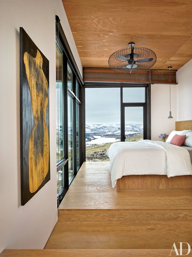 In a mountain home decorated by Olson Kundig Architects, the master bedroom is painted in a Benjamin Moore white, which picks up the color of the snow-covered mountains that can be glimpsed outside. | archdigest.com