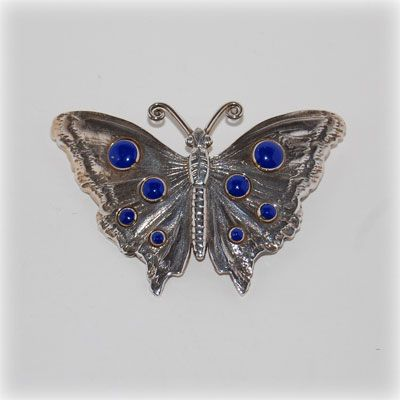 Handmade sterling silver butterfly brooch with lapis cabochon. Made in our workshop.