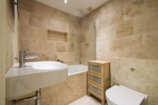A bathroom with travertine tiles and mosaics on the shower walls and floors