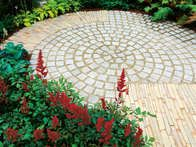 Granite pavers with a stone surround are an example of a natural paving choice suited to a traditional garden landscaping design.