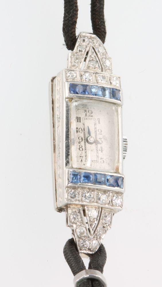 Lot 746M, A lady's platinum diamond and sapphire Art Deco cocktail watch on a silk bracelet, est £150-200