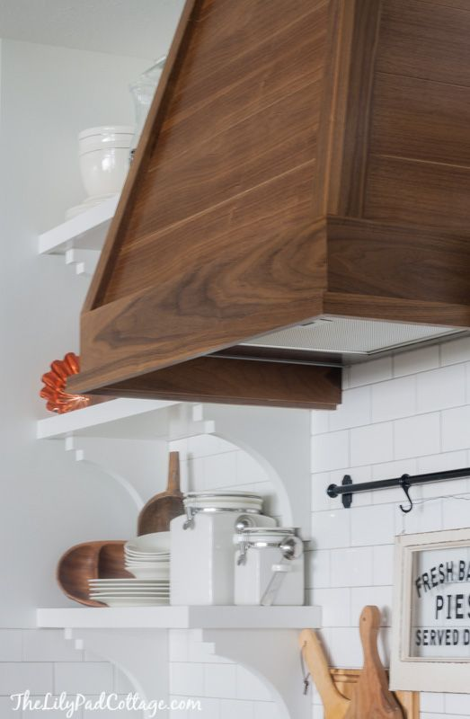 Wood Range Hood -  Basically, he built a a big wood box and then figured out the angles to cover the existing hood.  He used a router to cut grooves into the walnut plywood to make it look like planked boards – it is a lot cheaper to go that route.I wanted a wood tone to break up all the white in the kitchen, so he used walnut to match our floors.  I added 3 coats of satin water based clear poly to seal it.