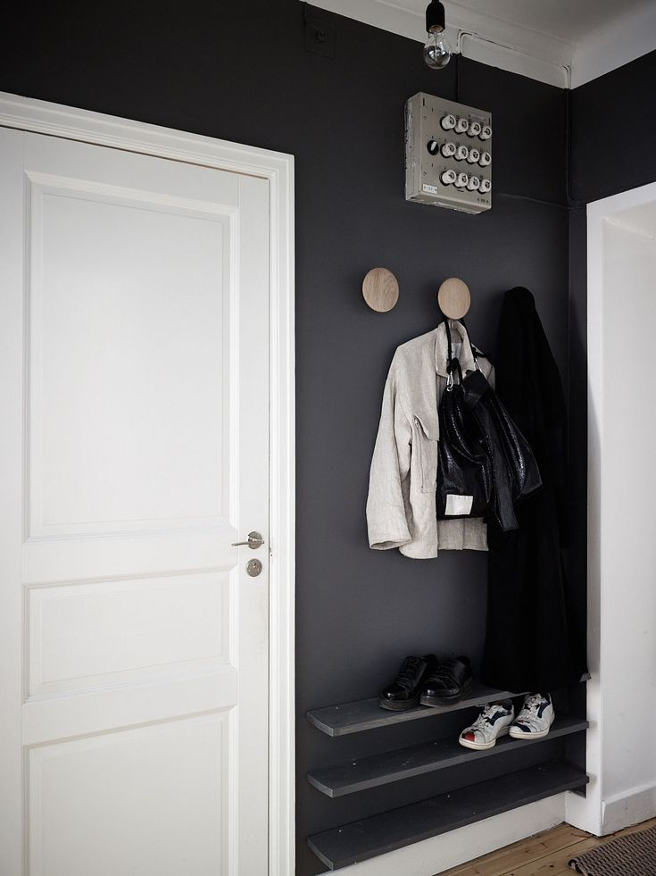 Above: In the entryway the designers created a mini landing pad by defining a sliver of wall with dark charcoal paint and installing a trio of Dots Wall Hooks by Muuto for hanging coats and bags and a trio of shelves for storing shoes.