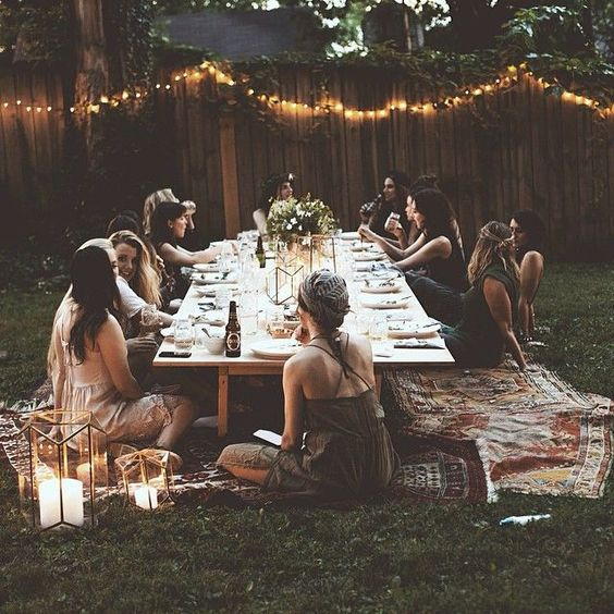 boho table setting with Christmas lights. Forget about chairs! Instead, choose a really low table and then add some pillows for seats. It would be better if you could add a bamboo or rattan mat underneath.
