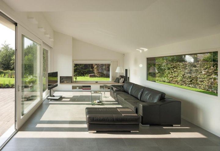 Il living è il punto più luminoso della casa, grazie alle ampie vetrate e alle finestre che regalano riposanti scorci sul verde. Il gusto è minimale e moderno, da richiesta dei committenti