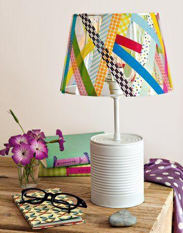 une lampe réalisée avec une boîte de conserve peinte en blanc et un abat-jour transparent habillé avec du masking tape, de ladhésif de toutes les couleurs et avec des motifs.