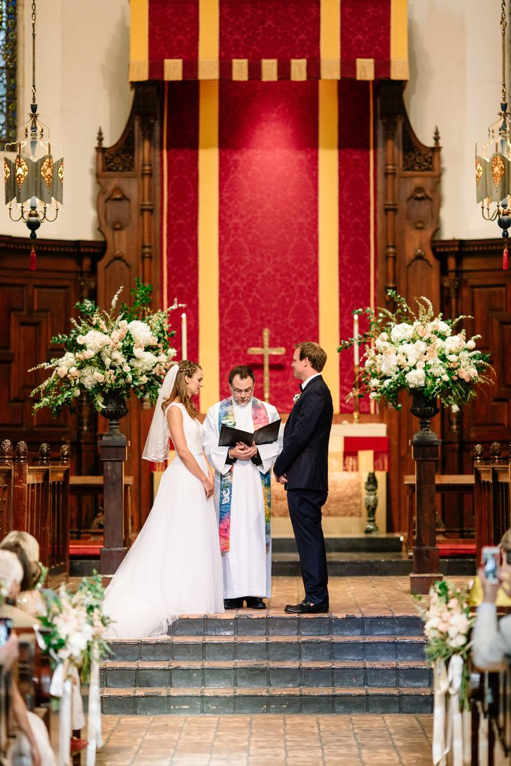 the bride and groom exchange vows in the historic chapel between large organic altar arrangements of white hydrangea, peach stock, white stock, la perla rose, vendela rose, spirea, French tulip, seeded eucalyptus & greenery in garden urns.