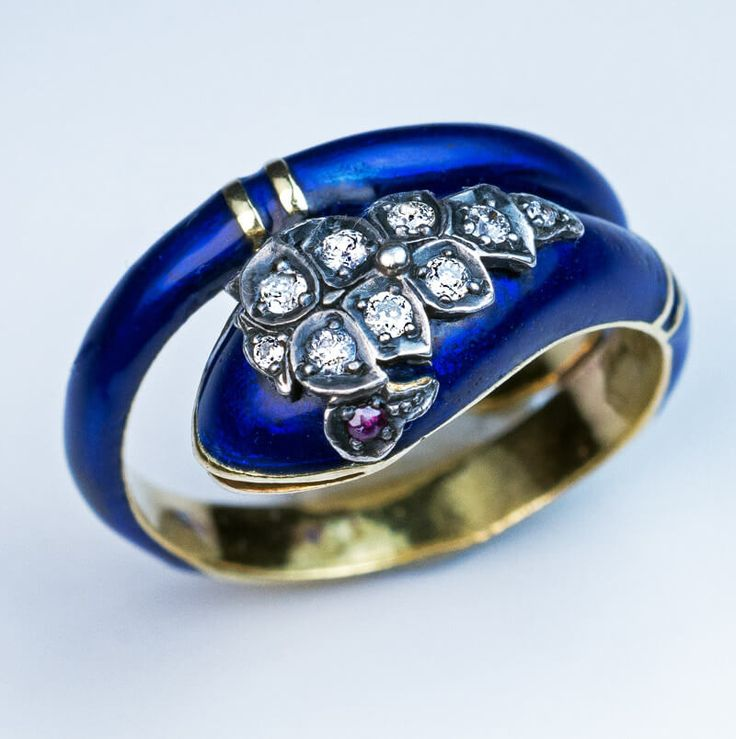circa 1890 A cobalt blue enamel and 18K yellow gold ring is designed as a coiled snake. The head of the snake is embellished with nine old European cut dia