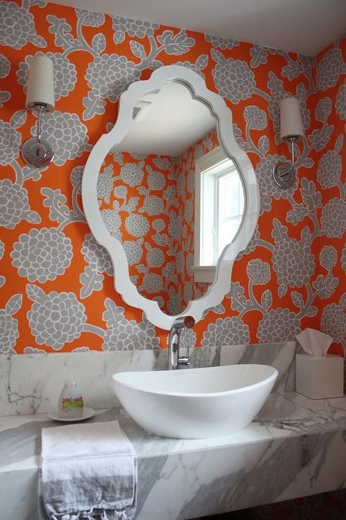 Fabulous bathroom boasts walls clad in orange and gray floral wallpaper lined with a Jonathan Adler Rococo Mirror over a statuary marble floating washstand topped with a bowl sink and gooseneck faucet.