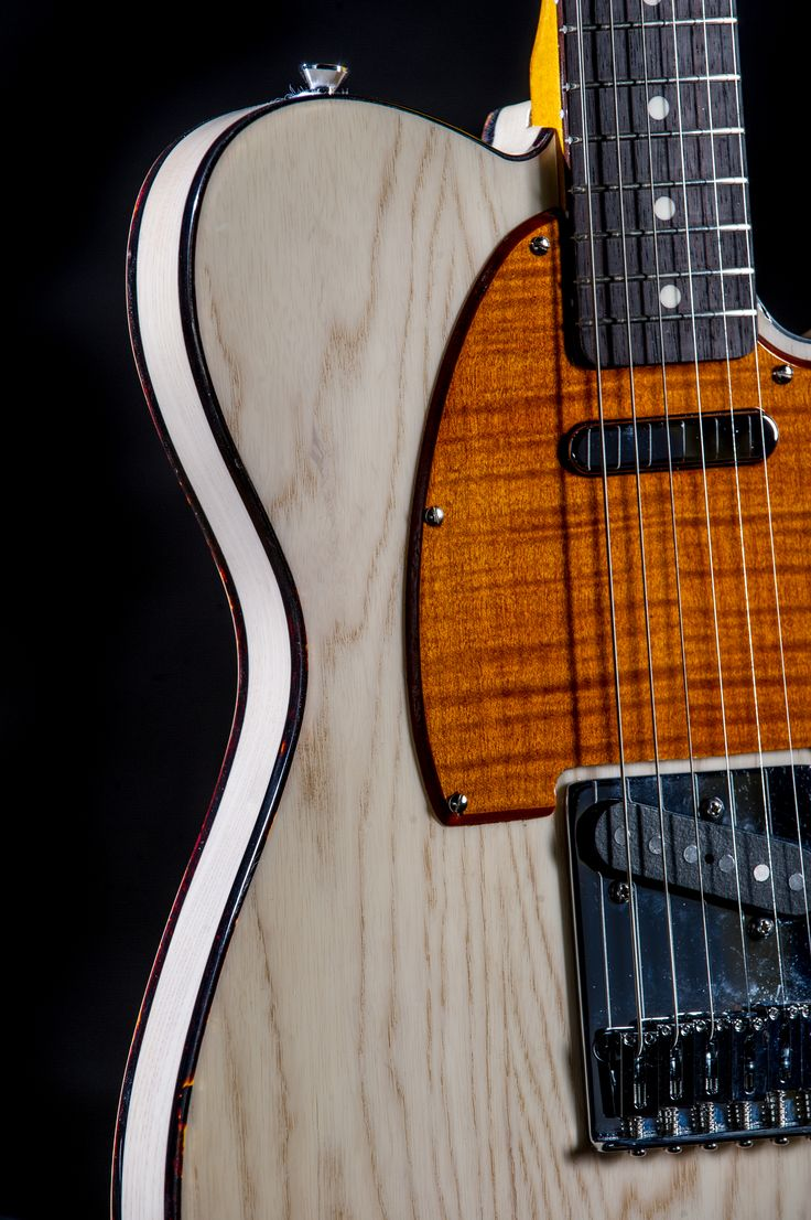 "One of our proprietary finishes! We call it ""Milk White"". This was done on an Ash wood Telecaster body, included with a burnt orange stained flamed maple pick guard."