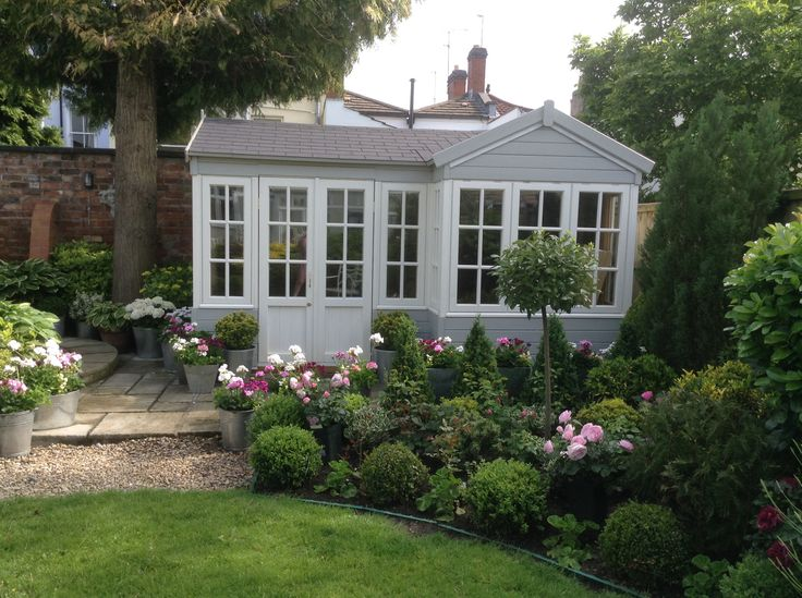 Summerhouse and newly planted Bed with Box Topiaries, Evergreen shrubs and David Austin Roses.