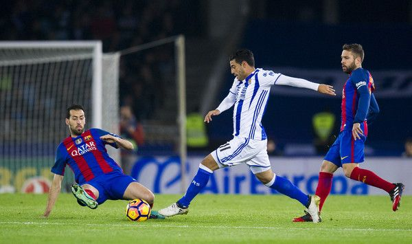 Sergio Busquets of FC Barcelona duels for the ball with Carlos Vela of Real Sociedad during the La Liga match between Real Sociedad de Futbol and FC Barcelona at Estadio Anoeta on November 27, 2016 in San Sebastian, Spain.