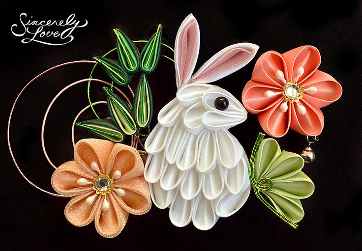 """An adorable and unique bunny fashioned in tsumami kanzashi style stands like an inquisitive visitor in a spring garden, framed in beautiful, vibrant flowers and lush green foliage. Sparkling organza fabric, glittering gems, and bright mizuhiki accents in shades of green and pink give life to the piece, finished by a gently chiming bell detail. Mounted on an alligator clip for easy wear, this kanzashi measures approximately 5.25"""" x 3.5""""."""