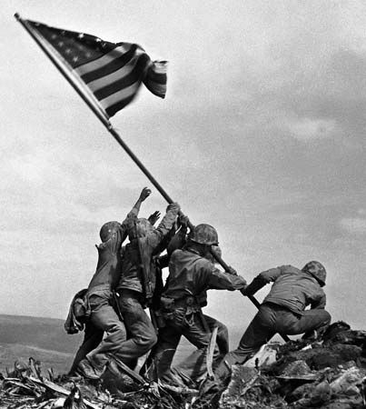 February 23, 1945 - US Marines raising the flag on Mt Surinsvhi on the Island of Iwo Jima. The flag was raised 4 days after the landing on February 19 the battle raged on for another 31 days ending on March 26, 1945.
