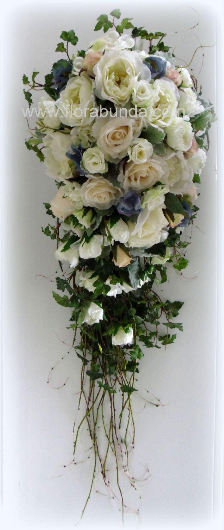 Large trailing wedding bouquet of artificial fake flowers. Hard to tell they are not real.