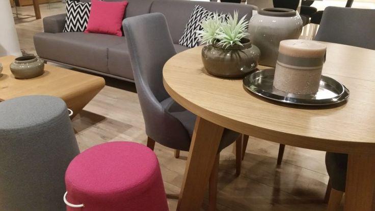 Okrągły drewniany stół z jasnego drewna w połączeniu z tapicerowanymi krzesłami w szarym kolorze. Szerokie oparcie przechodzące w podłokietniki zapewnią komfort podczas rodzinnych spotkań przy stole.