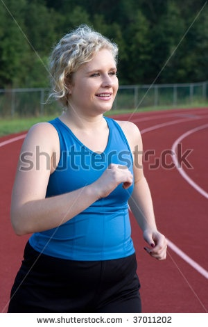 stock photo : A young woman who is somewhat overweight runs the track to burn calories.