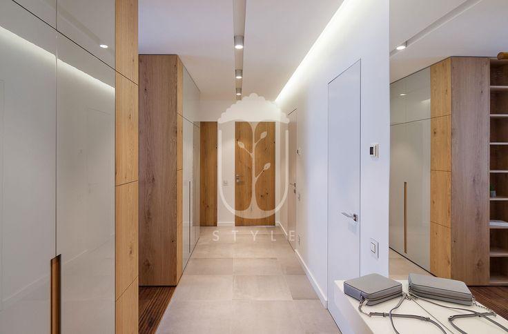 Пространство прихожей, переходящей в коридор, объединивший все помещения квартиры, формирует классическая палитра: серый, белый и цвет натурального дерева.