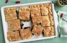 Olive nere e scarola racchiuse in un morbido guscio di pizza. Questa ricetta ci fa volare in Grecia.