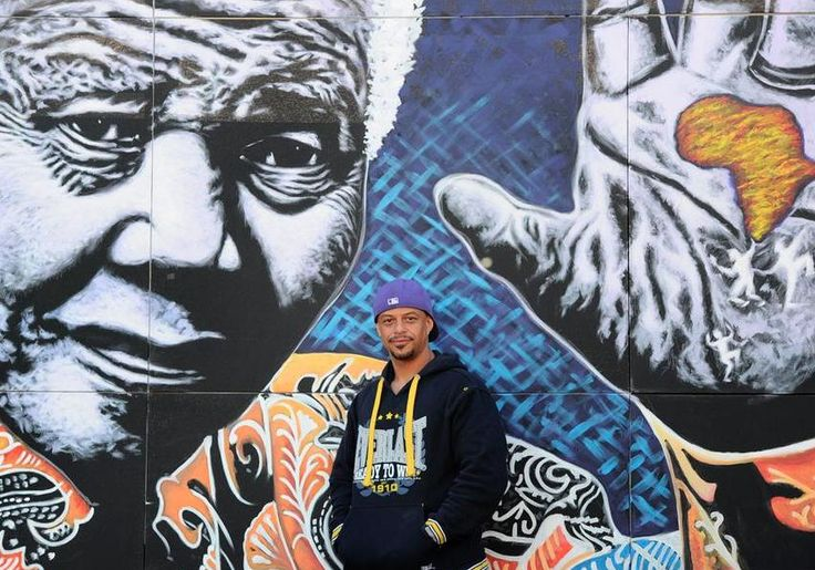 From The Citizen: Artist John Adams poses in-front of one of his paintings of Nelson Mandela at his home in Bosmont, 17 July 2013. The painting will be exhibited at the Future Ed education expo at the Dome, in Randburg, from the 25th to the 27th of July. Adams is donating some of the funds raised from the auction of the painting to the Teddy Bear Clinic and Sunlight Safe House. The painting measures 20 feet by 12 feet. Picture: Michel Bega