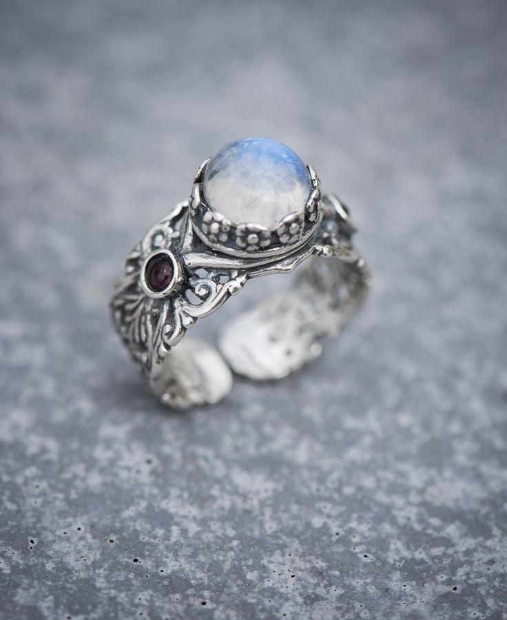 ring maansteen zilver - Een brede band van sierlijk opengewerkt zilver met als stralend middelpunt een grote maansteen, gevat in een krans van piepkleine bloemen.  Als je de witblauwe steen beweegt, zie je een zacht blauw schijnsel oplichten, waaraan maansteen zijn naam ontleent.