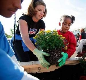Kathy Schwartz, wife of Detroit Lions head coach Jim Schwartz,  and CharlieBleu Saunders of Northville add flowers to a newly made flower bed.  The Detroit Lions Woman's Association and the Detroit Public Schools met at the Detroit Lions Academy on East Canfield in Detroit on Saturday, September 29, 2012 to build and plant flower beds.