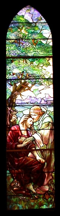 "The Good Samaritan The Good Samaritan window depicts the two principal characters from one of the most well-known examples of Jesus teaching through parables. Here the Samaritan tenderly consoles the robber's victim who had been left for dead along the dangerous road from Jerusalem to Samaria. Like the facing Benedicite Window, the Good Samaritan Window contains a landscape with spatial depth using a variety of extraordinary ""confetti"" glass. Extensive plating in the tree and the background,"