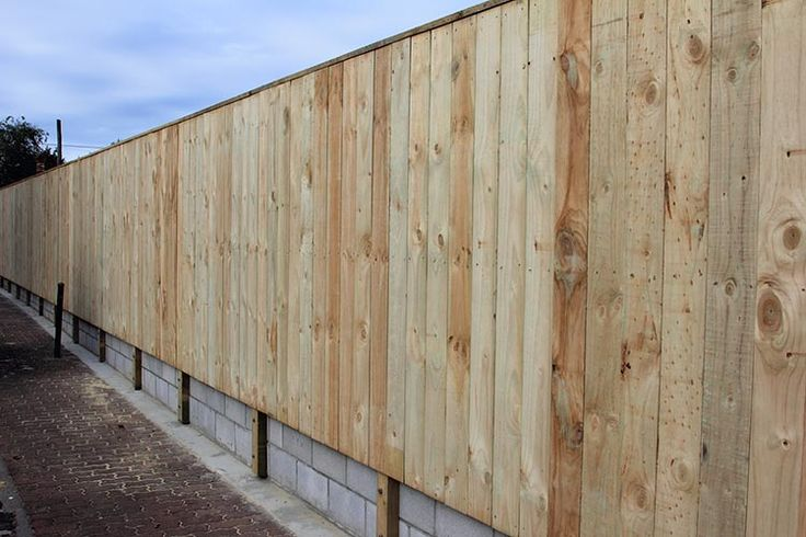Plain board wooden fence attached to block wall