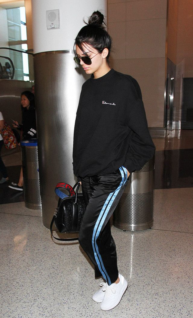 Kendall Jenner at LAX in satin track pants, oversized Vetements sweatshirt, and white sneakers