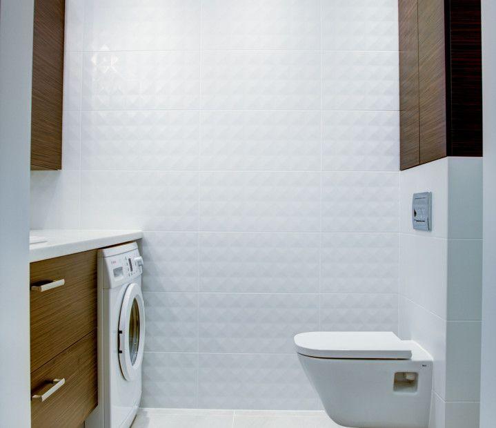 Drewniane elementy w łazience wśród białych płytek: drewniana szafka pod umywalkę oraz szafki nad toaletą.