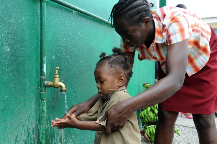 Marcia Gordon, a teacher at the UNICEF-supported Denham Town Basic School in the Denham Town community in the parish of Kingston and St. Andrew in Jamaica, helps a boy wash his hands at an outdoor water point outside the school. Many poor families cannot afford pre-school fees, books or uniforms, so their children do not attend school regularly. © UNICEF/Susan Markisz http://www.unicef.org: Book, Teacher