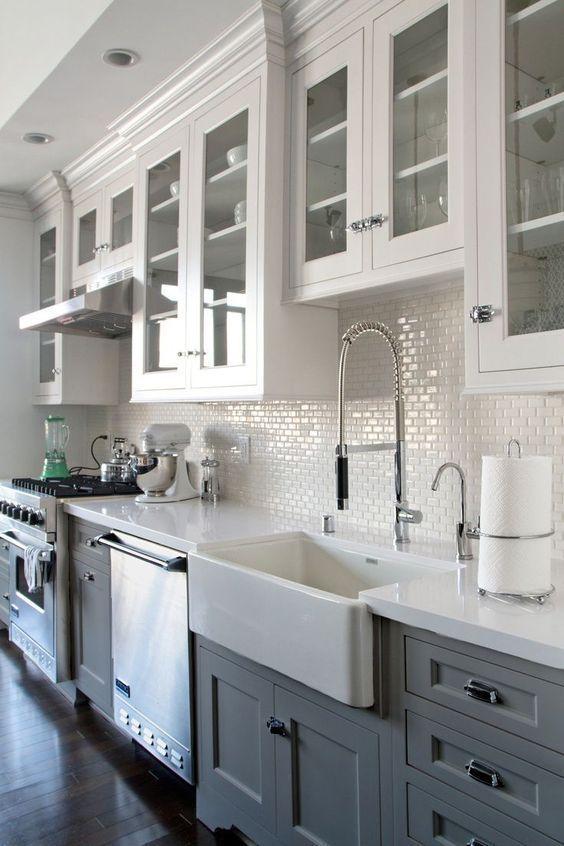 Grey/white kitchen w/ dark wood floors. Farmhouse sink.