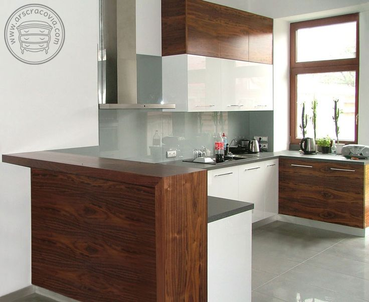 Kuchnia w fornirze amerykańskim i białym mdfie. Na ścianie szkło barwione, blaty pokryte laminatem HPL.
