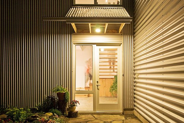 Gananoque Lake Road House - The 8 foot high front door is triple-glazed with a fiber-glass frame.  The open riser stairs take visitors from the front entry to the great room above.