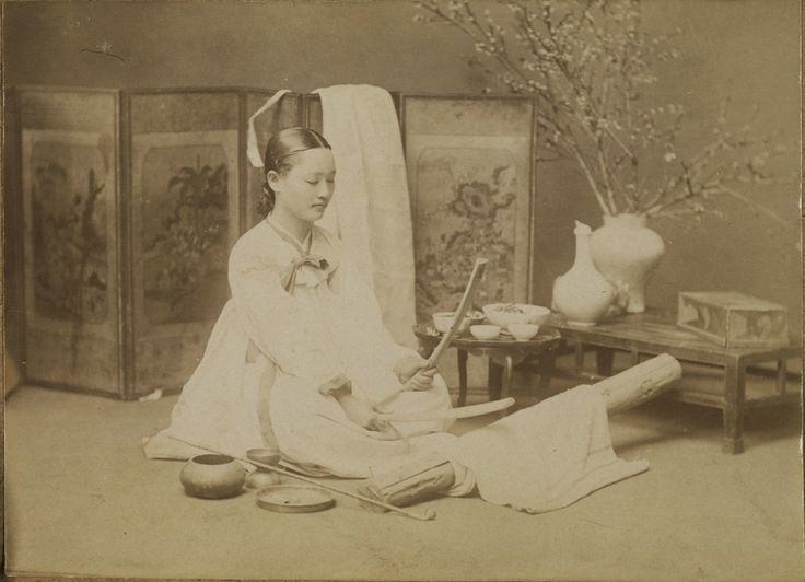[Woman fulling (ironing) clothes] 1904. Fulling clothes was done usually in the evenings, after the kitchen work was finished. When the clothes were still slightly damp after washing, they were folded and fulled on a flat board which is called 'tadumidol'. Women used a long and rounded wooden stick in each hand for fulling, which is called 'tadumi pangmangi'. As a result the clothes acquired a certain glossy surface sheen, which lasted for a considerable time. Cornell University Library