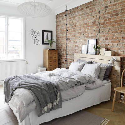 Dormitorio con pared ladrillo vista