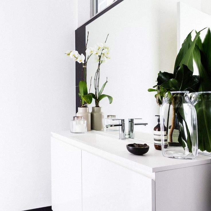 White bathroom with oversized mirror. White vanity and cabinetry. See more photos at stylecurator.com.au now