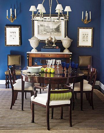 Dining room walls are Frank Blue by Sherwin-Williams — a conservative, masculine color that's sexy in this context. The mahogany table and chairs are 18th-century Regency; diamond-weave rug is from Dash & Albert.
