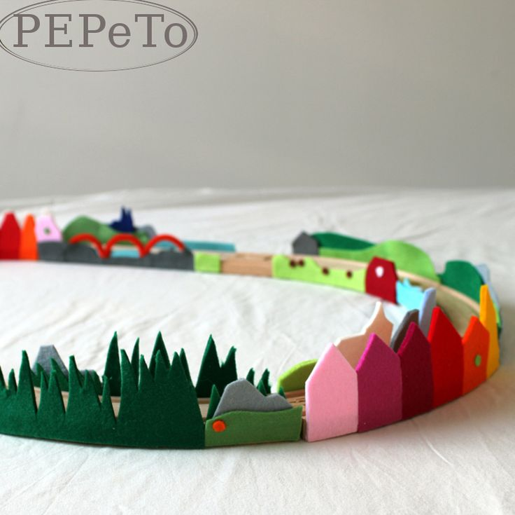 clever way to brighten up the wooden train sets.  If you add Velcro to the felt and the tracks, the children can customize the tracks as they want see fit.