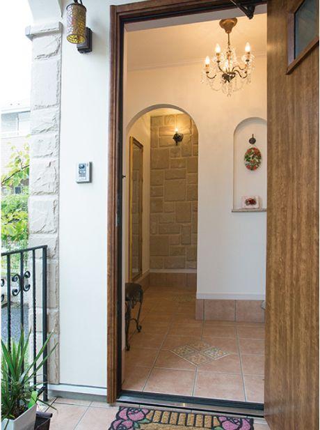 砂岩貼の壁が、石造りの城のような玄関。 アーチの奥はシューズクローゼットになっています。|デザイン|ナチュラル|タイル|
