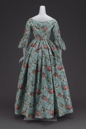 """Spitalfields brocade dress; dated """"mid-19th century, about 1840;"""" United States. MFA # 53.192. """"Fabric 18th century Spitalfields brocade, blue ground, horizontal interlacing ribbon and floral serpentines, brocaded with white and brilliant polychrome silks, tightly fitted bodice coming to V in center front, hooked down center back, wide flaring neckline, elbow length sleeves with sleeve ruffles shaped like those of the 18th century, full skirt with fullness gathered evenly all around."""""""