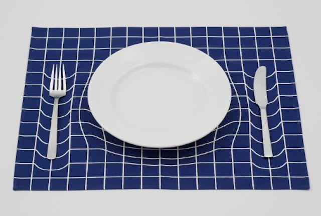 Graphic Warp Table Mat Ce set de table en tissu est un prototype pensé par A.P Works. La distorsion graphique qui compose le quadrillage du set semble être provoquée par le poids des éléments de la table, mais c'est bel et bien une ingénieuse illusion d'optique que le studio a mis en place, dans deux versions déclinées en bleu et blanc. À découvrir.
