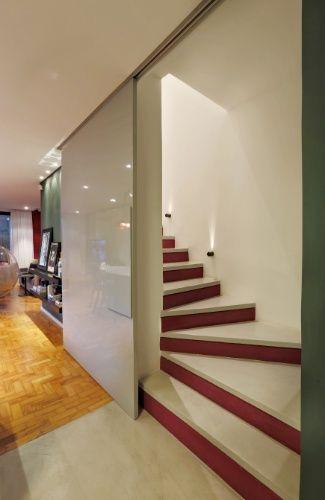 Quando aberta, a porta de correr dá acesso à escada que leva ao pavimento superior íntimo e esconde o armário para taças e louças (fotos 12 e 13). As escadas são revestidas com tecnocimento, mesmo material usado no piso da cozinha. O projeto de reforma é de Renata Popolo
