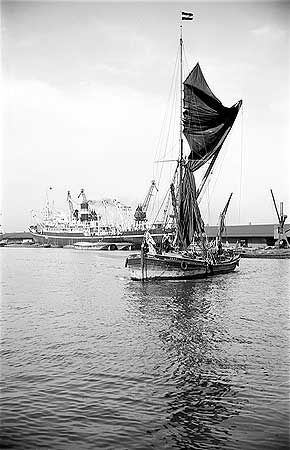 A Thames sailing barge named 'Henry' on the river with a larger ship moored on the dockside behind.  The Thames sailing barge was based on a Dutch design for easy handling in coastal and inland waters.