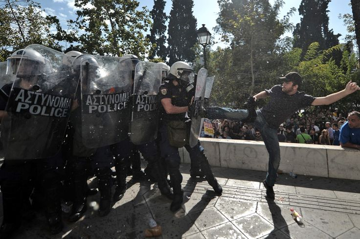 Kicking riot police in Greece. A man in Greece kicks riot police back. ImagebyARIS MESSINIS / Getty Images